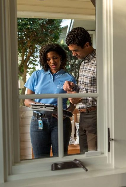 Man with home inspector in window
